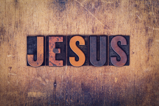 "The word ""Jesus"" written in dirty vintage letterpress type on a aged wooden background."